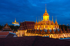 Wat Ratchanaddaram and Loha Prasat Metal Castle at dusk, Bangkok Stock Photo