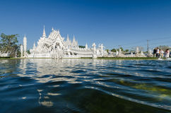 Wat Rong Khun a most famous white temple. CHIANGRAI, THAILAND - FEB 2 : Unidentified travelers visit Wat Rong Khun a most famous white temple in the North of Stock Image