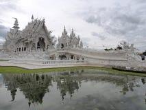 Wat Rong Khun (o templo branco) sob o céu nebuloso com reflexão da lagoa Foto de Stock