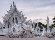Wat Rong Khun (o templo branco) sob o céu nebuloso com reflexão da lagoa Imagem de Stock Royalty Free