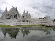 Wat Rong Khun (The White Temple) under cloudy sky with reflection from pond Stock Photo