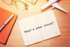 Wat is uw verhaal? notitieboekje met tekst bij blanco pagina op houten achtergrond met glazen en vliegtuigmodel royalty-vrije stock foto