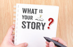 Wat uw verhaal is werk aan het witte notitieboekje van het ringsbindmiddel met hand Stock Fotografie