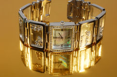 Watch. Woman brand watch on gold background with reflection Royalty Free Stock Image