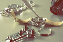 Watch battery replacement. Macro of replacing a watch battery with watchmaker tools Stock Image
