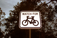 Watch for bicycles. White watch for bicycles sign with trees background at dusk Stock Photos