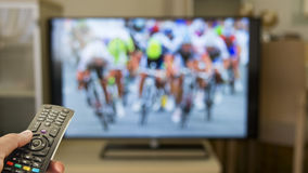 Watch bike race on TV. With remote control Stock Photos