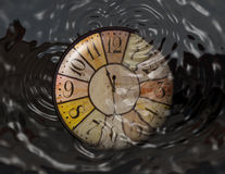 A watch is dropped in water. Concept of throwing time, wasting time. A watch is partially under water. There are some circles of water. Concept of waste of time Stock Photos