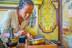 Watch the Ethiopian coffee ceremony. KIEV, UKRAINE - JUNE 4, 2017: The long process of hand coffee roasting, performing by young Ethiopian girl, the master of Stock Photography