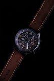 Watch expedition arrow with brown leather strap. On a black background stock photo