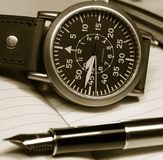 Watch and fountain pen. Vintage watch and pen over notebook selective focus on watch monochrome image stock photos