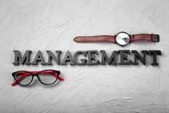 Watch, glasses and word \'Management\' composed from letters on textured background. Time management concept stock images