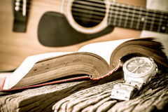 Watch and guitar with open book on old wooden table. Royalty Free Stock Photos
