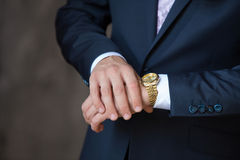 Watch on hands. Men's watch on the man's hands in a suit Royalty Free Stock Photo