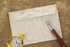 Watch and ink pen at envelope on sack background Royalty Free Stock Photo