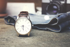 Watch, jeans and camera. Men watch, jeans and camera on wooden table Stock Image