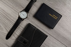 Watch with a leather strap, notebook, name card holder on a gray. Watch with a leather strap, notebook in leather cover, name card holder on a gray wooden Stock Image