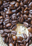 Watch in the lots of natural coffee beans Stock Images