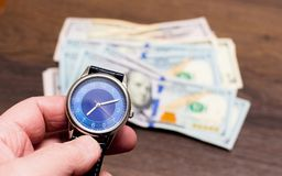 The watch is lying on dollars. Time to earn money. Time is money_. The watch is lying on dollars. Time to earn money. Time is money royalty free stock images