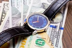 The watch is lying on dollars. Time to earn money. Time is money_. The watch is lying on dollars. Time to earn money. Time is money stock photography