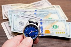 The watch is lying on dollars. Time to earn money. Time is money_. The watch is lying on dollars. Time to earn money. Time is money royalty free stock photos