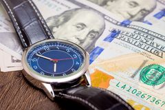 The watch is lying on dollars. Time to earn money. Time is money_. The watch is lying on dollars. Time to earn money. Time is money royalty free stock photography