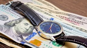 The watch is lying on dollars. Time to earn money. Time is money_. The watch is lying on dollars.  to earn money.  is money royalty free stock images