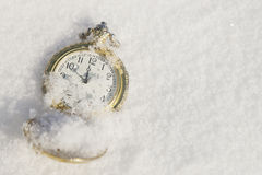 Watch lying in the snow before  new year Royalty Free Stock Photo