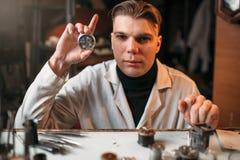 Watch maker holding wrist watch in hand Stock Photos