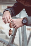 Watch on man hand. Fashion outdoor photo of stylish young handsome man with watch on hand and sunglasses on the other hand Stock Images
