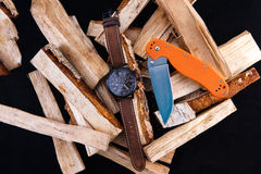 Watch mens on wood. Black dial. Knife with orange handle Stock Photo