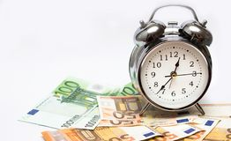 Watch and money isolate. Concept Time is money. An alarm clock, and European paper money, on a white background. Business concept, time is money royalty free stock photo