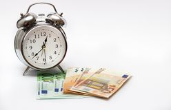 Watch and money isolate. Concept Time is money. An alarm clock, and European paper money, on a white background. Business concept, time is money stock photos