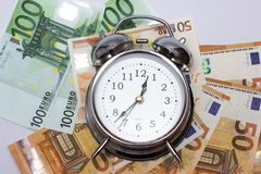 Watch and money isolate. Concept Time is money. An alarm clock, and European paper money, on a white background. Business concept, time is money stock image