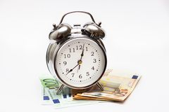 Watch and money isolate. Concept Time is money. An alarm clock, and European paper money, on a white background. Business concept, time is money stock photography