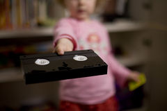Watch movies. Child showing a VHS tape with intention to watch a movie or a cartoon. Very shallow depth of field - focus on tape Royalty Free Stock Images