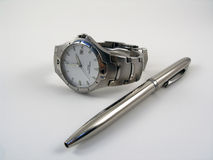 Watch near a ballpen Stock Images