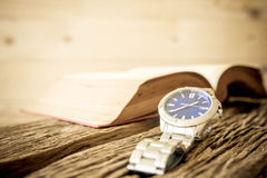 Watch with open book on old wooden table, vintage style Royalty Free Stock Image