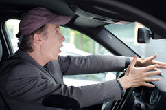 Watch out! Upset man driving and seeing something dangerous. Angry upset man protesting against something or someone while driving his car Stock Photography