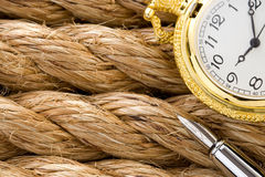 Watch with pen on ship ropes. Pocket watch with ink pen on ship ropes Stock Photography