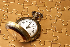 Watch and Puzzle. A pocket watch rests on a golden puzzle Stock Photos