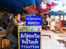 Watch repair shop. Unidentified watch repair and battery replacement booth at morning market in Vientiane, Laos Royalty Free Stock Photo