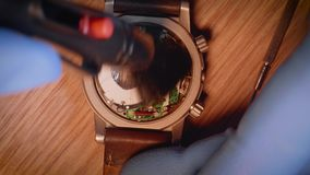 Watch repairer takes off case back of wristwatch and swipes it with little brush. Time Accuracy stock video