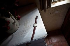 A watch sits on a kitchen table beside a window sill royalty free stock photos