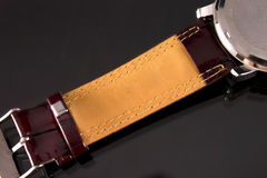 Watch strap. Closeup of watch strap in bordo on gray background royalty free stock images