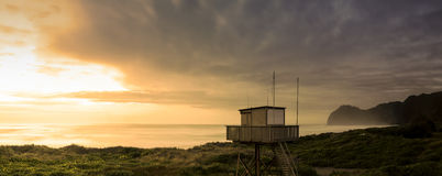 Watch Tower. Panoramic- for maximum quality- the lifesaver's watch tower at north piha at dusk just before a storm front moves in royalty free stock photo