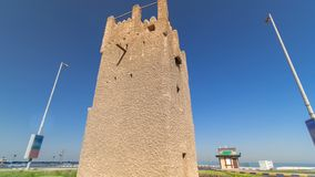 Watch tower of Ajman timelapse hyperlapse. United Arab Emirates. Watch tower of Ajman timelapse hyperlapse with blue sky and traffic. United Arab Emirates stock images