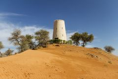 Watch tower on the sand dune that surrounding with trees at Abu Dhabi, UAE Stock Photo
