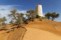 Watch tower on the sand dune that surrounding with trees at Abu Dhabi, UAE Royalty Free Stock Image