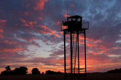 Watch tower on sunset sky. Background stock image